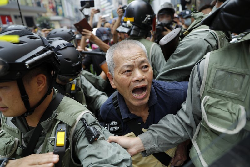 A protester is detained in Hong Kong on Sunday, Sept. 29, 2019. Protesters chanted slogans and heckled police as they were pushed back behind a police line. (AP Photo/Vincent Thian)