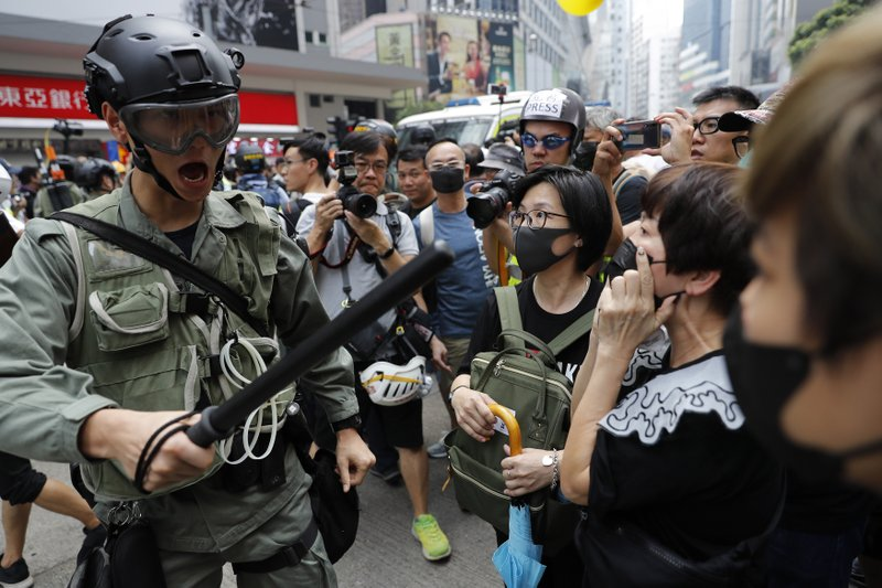 A police reacts to protesters in Hong Kong on Sunday, Sept. 29, 2019. Protesters chanted slogans and heckled police as they were pushed back behind a police line. (AP Photo/Vincent Thian)