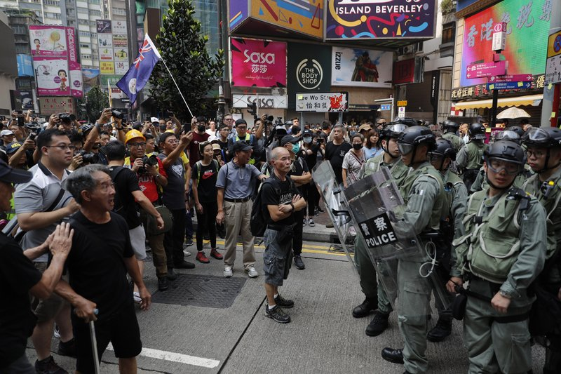 Protesters face off with police in Hong Kong on Sunday, Sept. 29, 2019. Protesters chanted slogans and heckled police as they were pushed back behind a police line. (AP Photo/Vincent Thian)