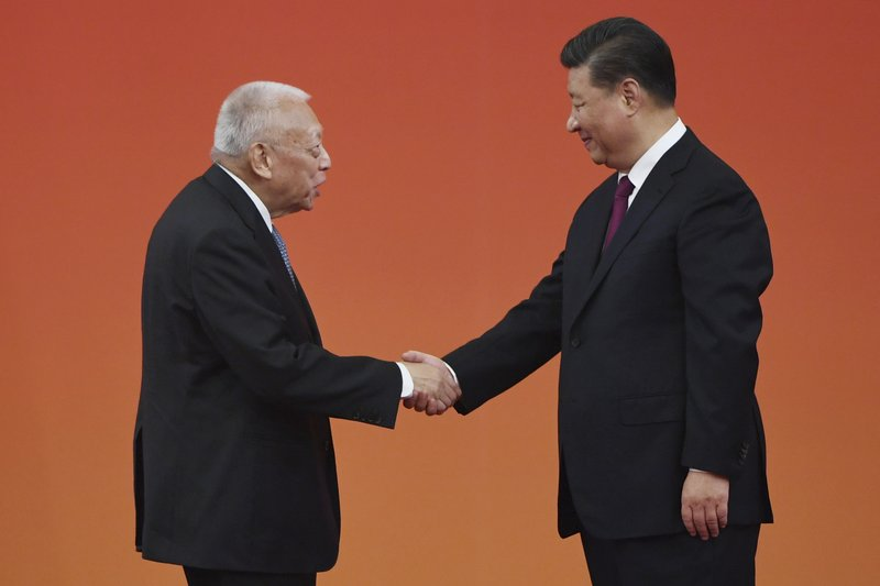 Chinese President Xi Jinping, right, presents an award to former Hong Kong Chief Executive Tung Chee-hwa during a ceremony in Beijing's Great Hall of the People Sunday, Sept. 29, 2019. Chinese President Xi Jinping awarded medals and honorary titles to an array of both domestic and international