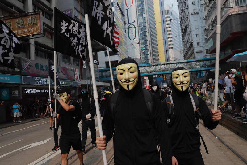 Protestors march wearing masks in Hong Kong on Sunday, Sept. 29, 2019. Sunday's gathering of protesters, a continuation of monthslong protests for greater democracy, is part of global