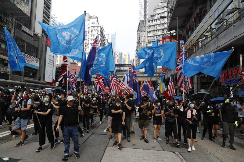 Protestors wave U.N.flags in Hong Kong, Sunday, Sept. 29, 2019.  Riot police fired tear gas Sunday after a large crowd of protesters at a Hong Kong shopping district ignored warnings to disperse in a second straight day of clashes, sparking fears of more violence ahead of China's National Day. (AP Photo/Vincent Thian)
