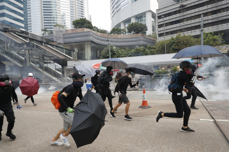 Protestors run as police use tear gas in Hong Kong, Sunday, Sept. 29, 2019. Riot police fired tear gas Sunday after a large crowd of protesters at a Hong Kong shopping district ignored warnings to disperse in a second straight day of clashes, sparking fears of more violence ahead of China's National Day. (AP Photo/Vincent Thian)