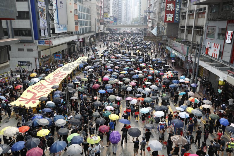Protestor holding umbrellas gather in Hong Kong, Sunday, Sept. 29, 2019. Protesters chanted slogans and heckled police as they were pushed back behind a police line. (AP Photo/Vincent Thian)
