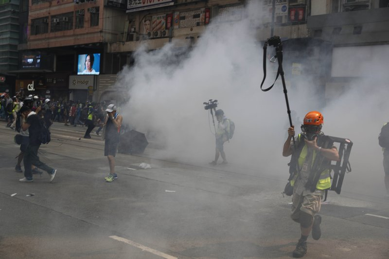 Journalists make their way through tear-smoke in Hong Kong, Sunday, Sept. 29, 2019. Protesters chanted slogans and heckled police as they were pushed back behind a police line. (AP Photo/Vincent Thian)