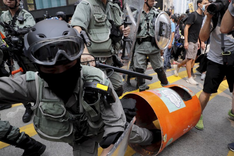 A Hong Kong police officer steps into a trash bin by accident as they confront protesters in Hong Kong on Sunday, Sept. 29, 2019. Sunday's gathering of protesters, a continuation of monthslong protests for greater democracy, is part of global