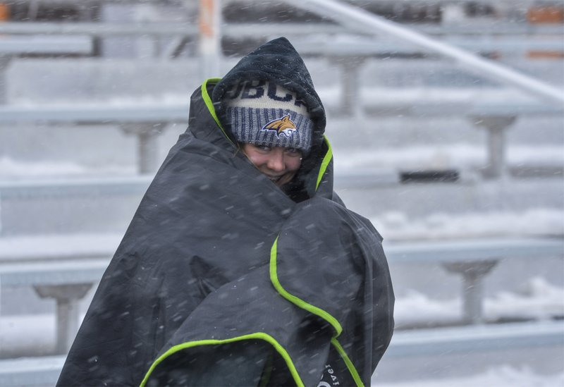Fans brace against the wind and snow at a football game between Centerville High School and Belt High School, Saturday, Sept. 28, 2019, in Centerville, Mont. Strong winds and heavy snow caused power outages and temporary road closures in northwestern Montana as a wintry storm threatened to drop several feet of snow in some areas of the northern Rocky Mountains. (Rion Sanders/The Great Falls Tribune via AP)