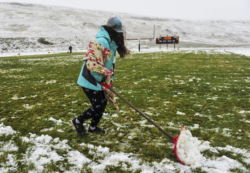 Ne'vaeh Allison clears snow from the Centerville High School football field before the school's game against Belt High in Centerville, Mont., Saturday, Sept. 28, 2019. Strong winds and heavy snow caused power outages and temporary road closures in northwestern Montana as a wintry storm threatened to drop several feet of snow in some areas of the northern Rocky Mountains. (Rion Sanders/The Great Falls Tribune via AP)