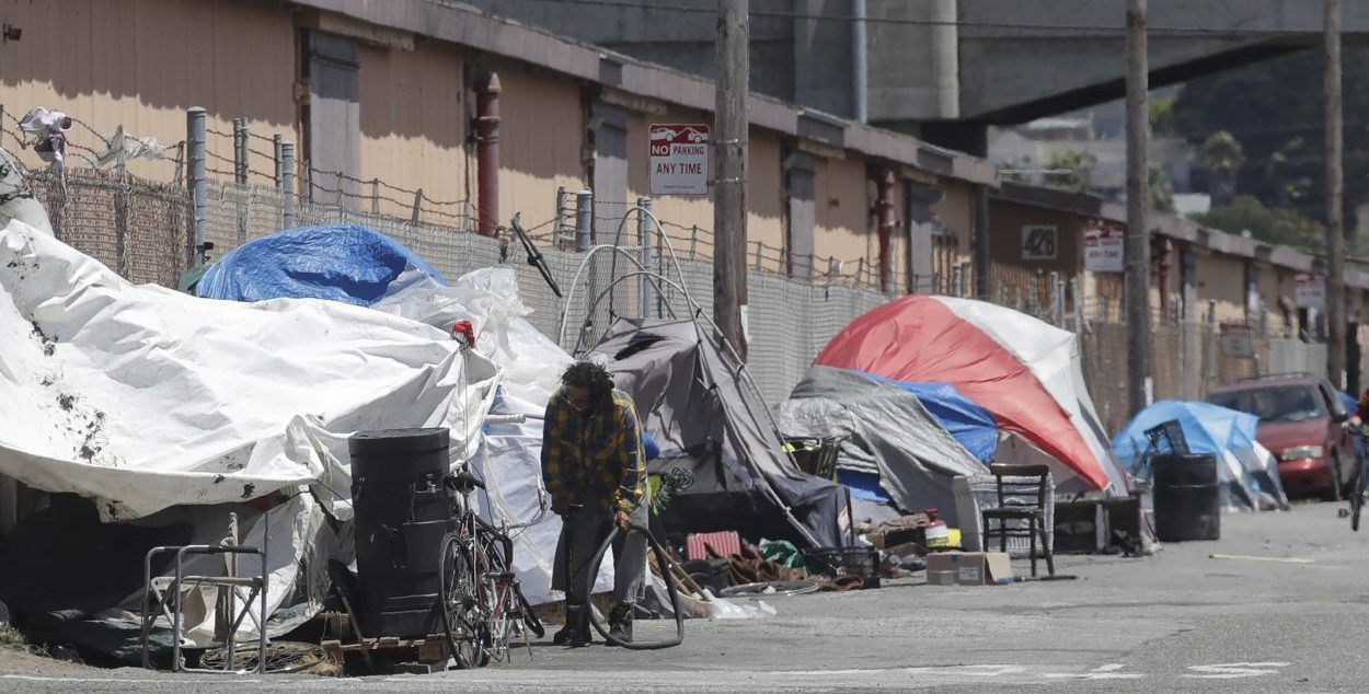 The photo shows a man holding a bicycle tire outside a tent along a street in San Francisco. (AP / Jeff Chiu, File)