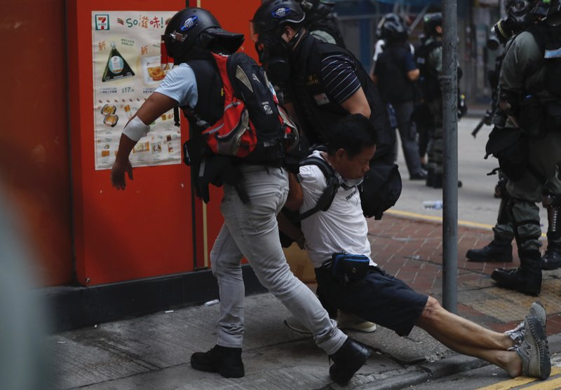 An injured anti-government protester is attended to by others during a clash with police in Hong Kong, Tuesday, Oct. 1, 2019. Thousands of black-clad protesters marched in central Hong Kong as part of multiple pro-democracy rallies Tuesday urging China's Communist Party to