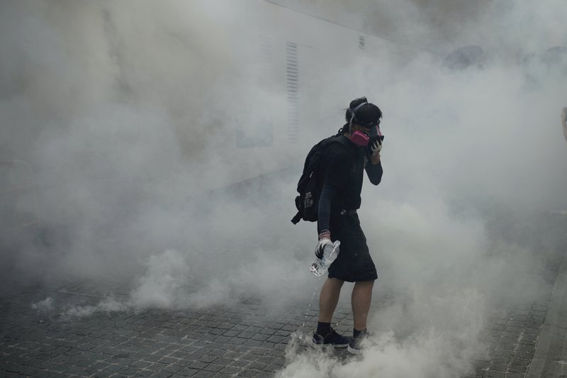 An anti-government protester walks through tear gas smoke during a clash with police at the Wong Tai Sin area in Hong Kong, Tuesday, Oct. 1, 2019. Thousands of black-clad pro-democracy protesters defied a police ban and marched in central Hong Kong on Tuesday, urging China's Communist Party to