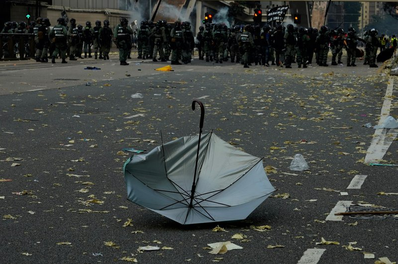 An anti-government protester's umbrella lies on the ground after a clash with police in Hong Kong, Tuesday, Oct. 1, 2019. Thousands of black-clad protesters marched in central Hong Kong as part of multiple pro-democracy rallies Tuesday urging China's Communist Party to