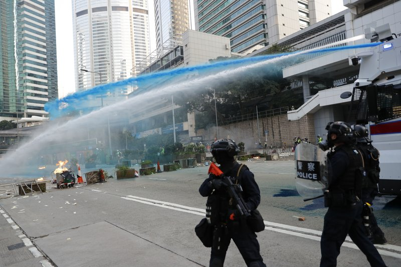Police use blue dyed water to disperse anti-government protesters in Hong Kong, Tuesday, Oct. 1, 2019. Thousands of black-clad protesters marched in central Hong Kong as part of multiple pro-democracy rallies Tuesday urging China's Communist Party to