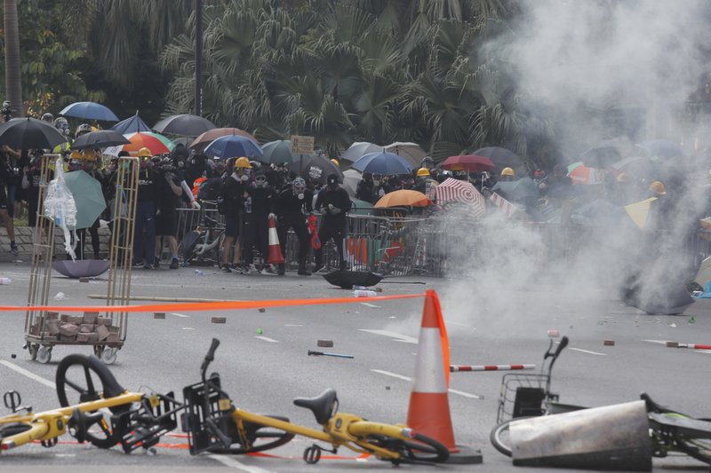 Police fire tear gas at anti-government protesters at Shatin, Hong Kong, Tuesday, Oct. 1, 2019. Thousands of black-clad pro-democracy protesters defied a police ban and marched in central Hong Kong on Tuesday, urging China's Communist Party to