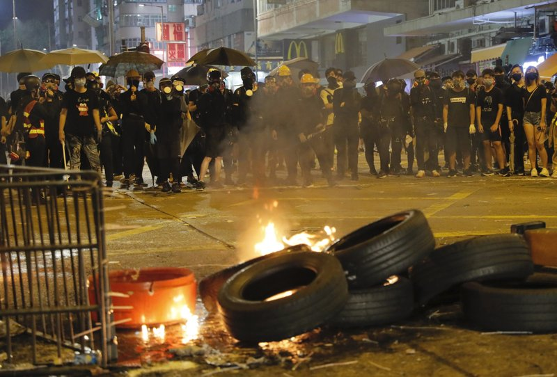 Black-clad protestors stand near burning tires in Hong Kong, Tuesday, Oct. 1, 2019. A Hong Kong police official says a pro-democracy protester was shot when an officer opened fire with his revolver during clashes Tuesday. A video of the incident, shot by the City University Student Union and shared on social media, shows a dozen black-clad protesters hurling objects at a group of riot police pursuing them. One officer, who was surrounded, drew his revolver and pointed it at the group. He fired and one protester collapsed on the street while others fled. (AP Photo/Kin Cheung)