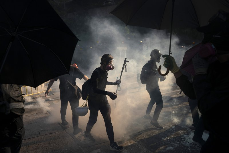 Black-clad protestors stand surrounded by smoke from tear gas shells in Hong Kong, Tuesday, Oct. 1, 2019. Hong Kong police shot a protester at close range, leaving him bleeding from his shoulder and howling on the ground, in a fearsome escalation of anti-government demonstrations that spread across the semi-autonomous Chinese territory on Tuesday. Tens of thousands marched in a day of rage as Communist leaders in Beijing celebrated 70 years in power. (AP Photo/Felipe Dana)