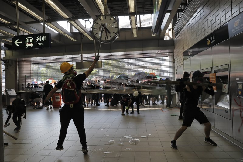 Anti-government protesters vandalize a MTR public transport station in Hong Kong, Tuesday, Oct. 1, 2019. In a fearsome escalation of violence, Hong Kong police shot a protester at close range in the chest Tuesday, leaving the teenager bleeding and howling on the ground. Tens of thousands joined anti-government demonstrations that spread across the semi-autonomous Chinese territory even as Communist leaders in Beijing celebrated 70 years in power. (AP Photo/Kin Cheung)