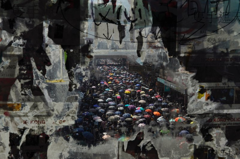 Marching anti-government protesters are seen through a glass with peeled off posters   , Tuesday, Oct. 1, 2019, in Hong Kong while the celebration of the People's Republic's 70th anniversary is taking place in Beijing. Police are warning of the potential for protesters to engage in violence