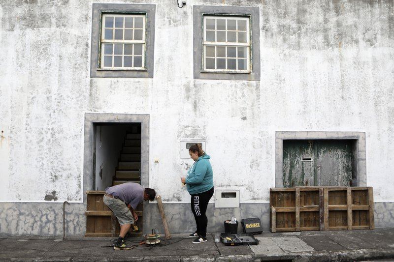 Residents board up a door in preparation for the arrival of hurricane Lorenzo in Horta, the capital of the Portuguese island of Faial, Tuesday, Oct. 1, 2019. The Category 2 hurricane is expected to hit the Atlantic Ocean Portuguese archipelago of the Azores Tuesday night and Wednesday morning. Lorenzo was previously a Category 5 hurricane, the strongest storm ever observed so far north and east in the Atlantic basin. (AP Photo/Joao Henriques)