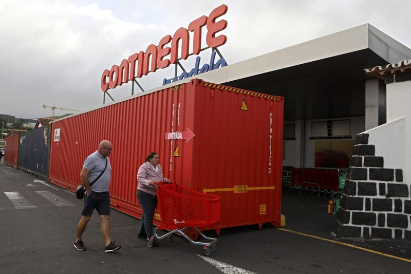 Customers enter a supermarket past containers positioned along its front window in preparation for the arrival of hurricane Lorenzo in Horta, the capital of the Portuguese island of Faial, Tuesday, Oct. 1, 2019. The Category 2 hurricane is expected to hit the Atlantic Ocean Portuguese archipelago of the Azores Tuesday night and Wednesday morning. Lorenzo was previously a Category 5 hurricane, the strongest storm ever observed so far north and east in the Atlantic basin. (AP Photo/Joao Henriques)