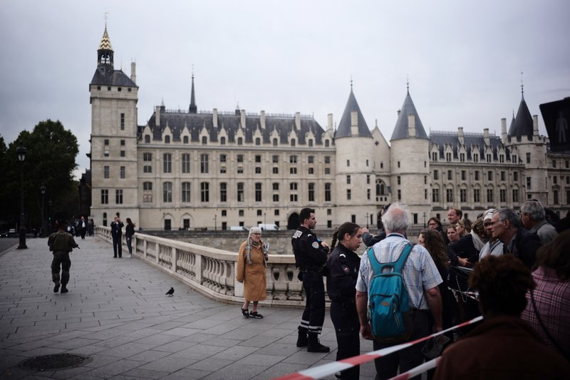 People stand behind a police tape as they are evacuated nearby the police headquarters after an incident in Paris, Thursday, Oct. 3, 2019. A French police union official says an attacker armed with a knife has killed one officer inside Paris police headquarters before he was shot and killed. (AP Photo/Kamil Zihnioglu)