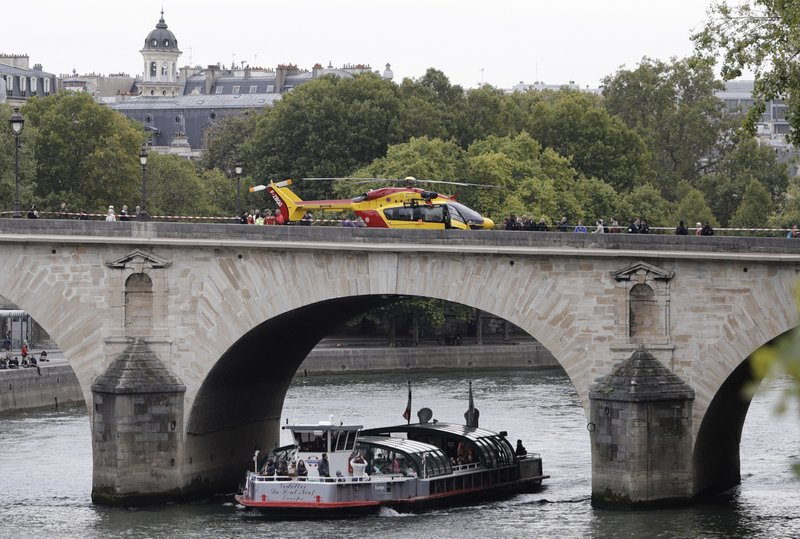 A helicopter is parked on the Pont Marie bridge after an incident at the police headquarters in Paris, Thursday, Oct. 3, 2019. A French police union official says an attacker armed with a knife has killed one officer inside Paris police headquarters before he was shot and killed. (AP Photo/Kamil Zihnioglu)