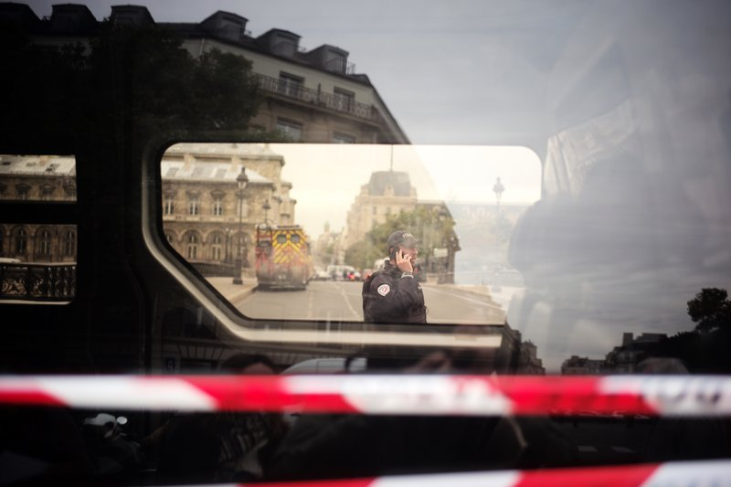 A police officer uses his phone near the Paris police headquarters, left, Thursday, Oct.3, 2019. A union official says 4 police officers have died in a knife attack by an employee at Paris police headquarters. (AP Photo/Kamil Zihnioglu)