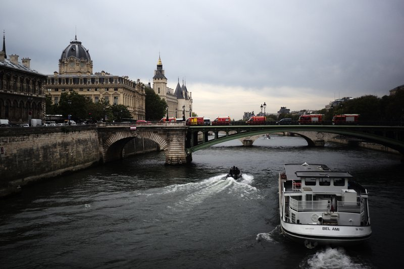 Rescue vehicles park on the bridge leading to the Paris police headquarters, left, Thursday, Oct.3, 2019. A union official says 4 police officers have died in a knife attack by an employee at Paris police headquarters. (AP Photo/Kamil Zihnioglu)
