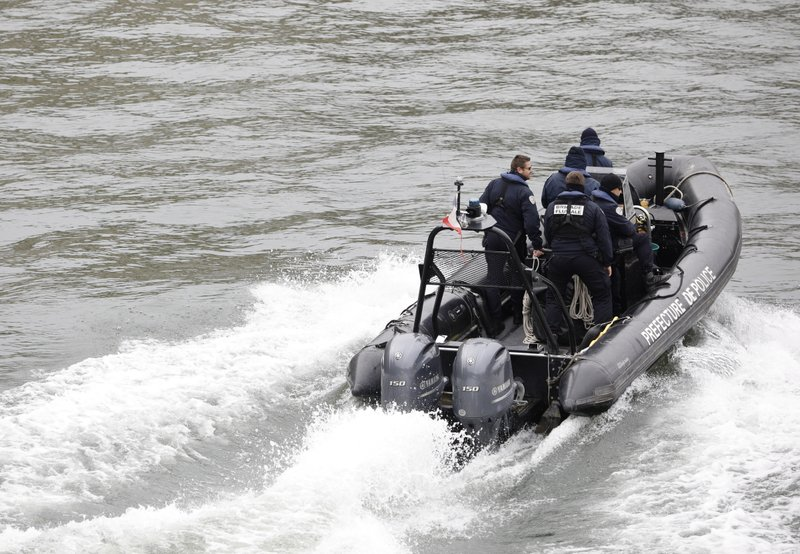 Police officers patrol in a rubber boat on the Seine river after an incident at the police headquarters in Paris, Thursday, Oct. 3, 2019. A French police union official says an attacker armed with a knife has killed one officer inside Paris police headquarters before he was shot and killed. (AP Photo/Kamil Zihnioglu)