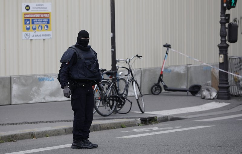 A masked police officer stands next to a police tape after an incident in Paris, Thursday, Oct. 3, 2019. A French police union official says an attacker armed with a knife has killed one officer inside Paris police headquarters before he was shot and killed. (AP Photo/Kamil Zihnioglu)
