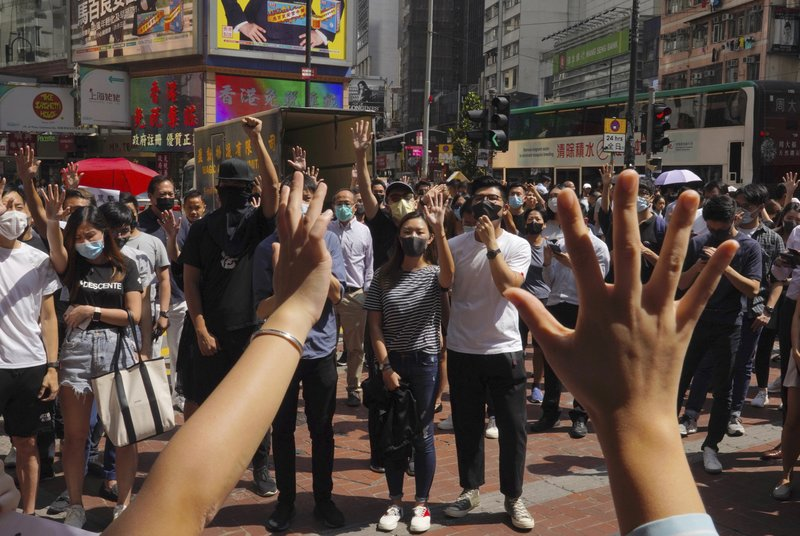 Protesters wear masks and hold up their hands to represent their five demands in Hong Kong Friday, Oct. 4, 2019. Hong Kong pro-democracy protesters marched in the city center Friday ahead of plans by the city's embattled leader to deploy emergency powers to ban people from wearing masks in a bid to quash four months of anti-government demonstrations. (AP Photo/Vincent Yu)