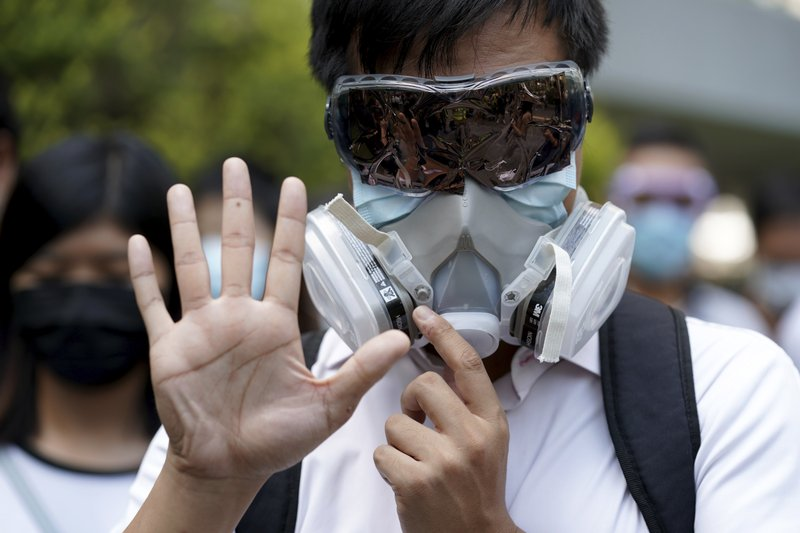 A protester wears a gas mask and holds up his hand to represent the protester's five demands in Hong Kong Friday, Oct. 4, 2019. Hong Kong pro-democracy protesters marched in the city center ahead of reported plans by the city's embattled leader to deploy emergency powers to ban people from wearing masks in a bid to quash four months of anti-government demonstrations. (AP Photo/Vincent Thian)