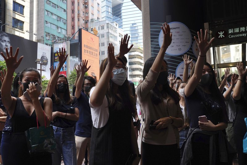 Protesters wear masks and hold up their hands to represent the protesters' five demands in Hong Kong on Friday, Oct. 4, 2019. Hong Kong pro-democracy protesters marched in the city center ahead of reported plans by the city's embattled leader to deploy emergency powers to ban people from wearing masks in a bid to quash four months of anti-government demonstrations. (AP Photo/Vincent Yu)