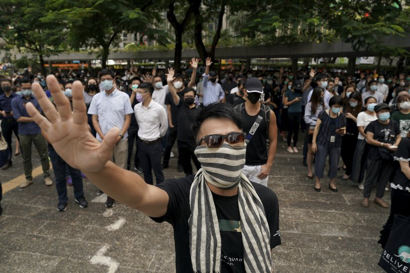 A protester covers up his face and holds up his hand to represent the five demands in Hong Kong Friday, Oct. 4, 2019. Hong Kong pro-democracy protesters marched in the city center ahead of reported plans by the city's embattled leader to deploy emergency powers to ban people from wearing masks in a bid to quash four months of anti-government demonstrations. (AP Photo/Vincent Thian)