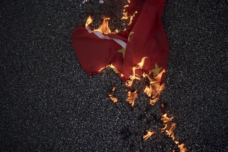 A Chinese national flag burns on the road in Hong Kong on Friday, Oct. 4, 2019. Thousands of protesters in masks are streaming into Hong Kong streets after the territory's leader invoked rarely used emergency powers to ban masks at rallies. (AP Photo/Felipe Dana)