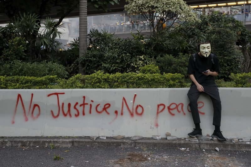 A masked protester sits near graffiti during a protest in Hong Kong, Friday, Oct. 4, 2019. Hong Kong Chief Executive Carrie Lam announced that protesters are banned from wearing masks to conceal their identities in a hardening of the government's stance against the 4-month-old demonstrations. (AP Photo/Kin Cheung)