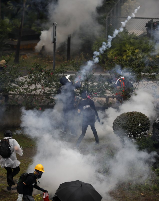 Protesters throw back tear gas at police in Hong Kong, Sunday, Oct. 6, 2019. Shouting
