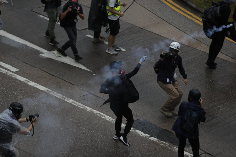 A protestor throws back teargas shell at police in Hong Kong, Sunday, Oct. 6, 2019. Shouting
