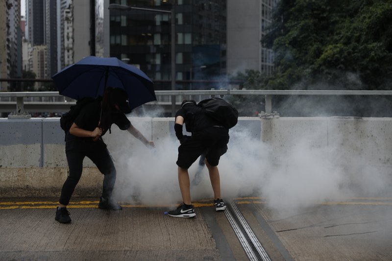 Police use teargas to disperse protestors in Hong Kong, Sunday, Oct. 6, 2019. Shouting