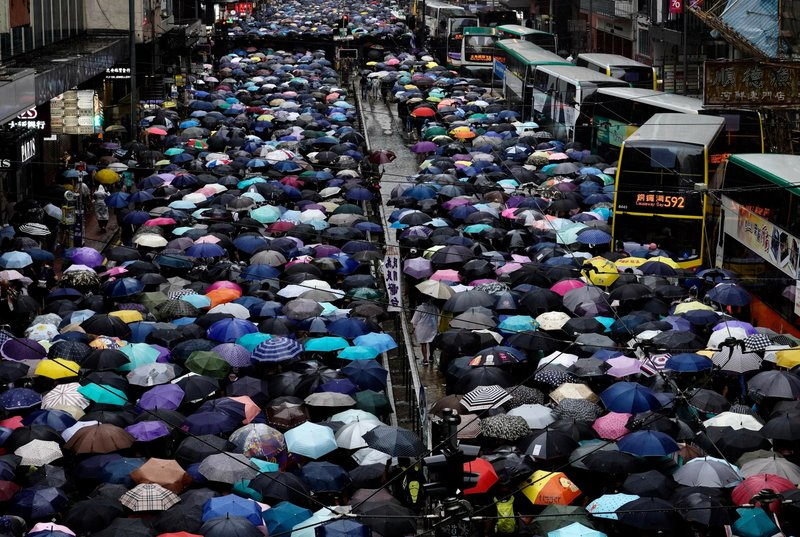 Anti-government protesters holding umbrellas take part in a march in Hong Kong, Sunday, Oct. 6, 2019. A group of pro-democracy Hong Kong legislators filed a legal challenge against the government's use of a colonial-era emergency law to criminalize the wearing of masks at rallies to quell anti-government demonstrations, which diminished in intensity but didn't stop. (AP Photo/Vincent Yu)