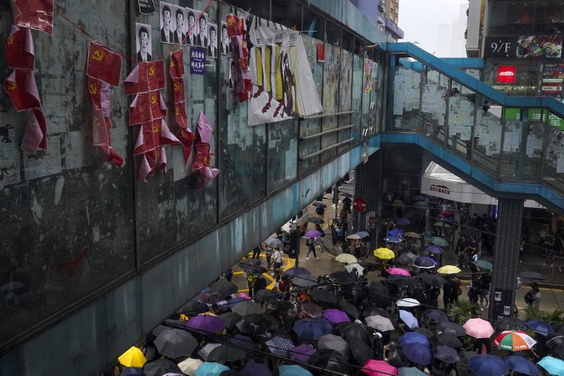 Protesters carrying umbrellas march past a pedestrian walk bridge displaying photos of tainted Chinese President Xi Jinping and communist party flags in Hong Kong, Sunday, Oct. 6, 2019. Thousands of protesters braved the rain to march in central Hong Kong as a second legal attempt to block a mask ban at rallies to quash four months of pro-democracy demonstrations was rejected by the court. (AP Photo/Vincent Yu)