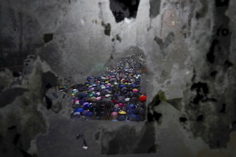 Protesters carrying umbrellas are seen through the tainted glass panel on the pedestrian overhead bridge as they march on a street in Hong Kong, Sunday, Oct. 6, 2019. Thousands of protesters braved the rain to march in central Hong Kong as a second legal attempt to block a mask ban at rallies to quash four months of pro-democracy demonstrations was rejected by the court. (AP Photo/Vincent Yu)