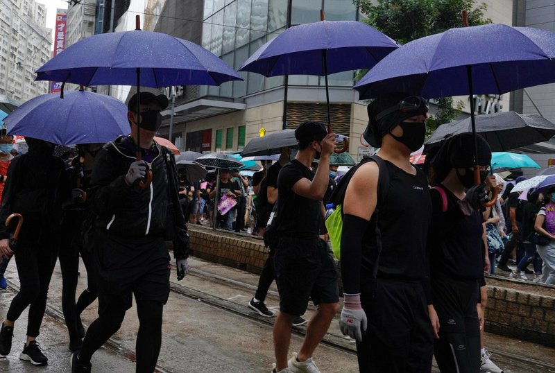 Anti-government protesters wearing masks and holding umbrellas march in Hong Kong, Sunday, Oct. 6, 2019. A group of pro-democracy Hong Kong legislators filed a legal challenge against the government's use of a colonial-era emergency law to criminalize the wearing of masks at rallies to quell anti-government demonstrations, which diminished in intensity but didn't stop. (AP Photo/Vincent Yu)