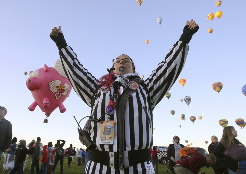 A Zebra or launch director gives the thumbs up to a balloonist for lift-off at the Albuquerque International Balloon Fiesta in Albuquerque, N.M., Sunday, Oct. 6, 2019. (Jerry Larson/Waco Tribune-Herald via AP)