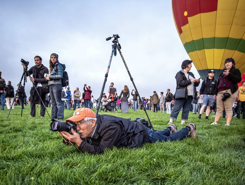 Akira Otaka, foreground, a photographer from Japan who has been photographing each balloon fiesta since 1992, works at the 2019 Albuquerque International Balloon Fiesta on Saturday, Oct. 5, 2019, Albuquerque, N.M. The spectacle has grown over nearly five decades and infuses millions of dollars into the economy each year. The fiesta is one of the most photographed events in the world, but drones are strictly prohibited.  (Roberto E. Rosales/The Albuquerque Journal via AP)