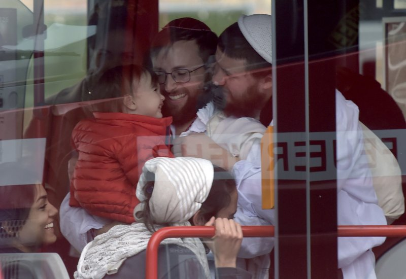 People, wearing traditional Jewish clothing, react after they were escorted to a bus at a Jewish cemetery and synagogue in Halle, Germany, Wednesday, Oct. 9, 2019. One or more gunmen fired several shots on Wednesday in the German city of Halle. Police say a person has been arrested after a shooting that left two people dead. (AP Photo Jens Meyer)