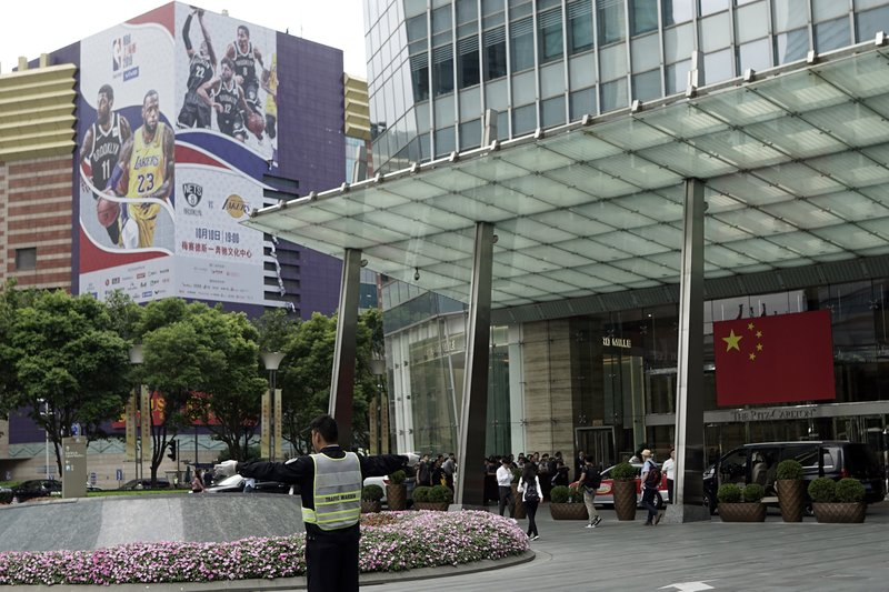 An official directs traffic near a Chinese flag and a billboard advertising an NBA preseason basketball game on Thursday between the Los Angeles Lakers and Brooklyn Nets in Shanghai, China, Wednesday, Oct. 9, 2019. The NBA has postponed Wednesday's scheduled media sessions in Shanghai for the Brooklyn Nets and Los Angeles Lakers, and it remains unclear if the teams will play in China this week as scheduled. (AP Photo)