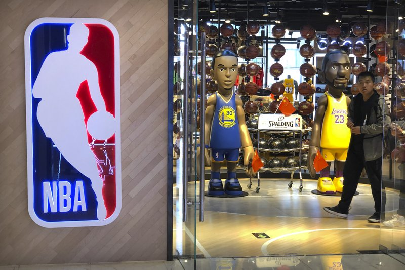A man walks past statues of NBA players Stephen Curry of the Golden State Warriors, left, and Lebron James of the Los Angeles Lakers holding Chinese flags in the entrance of an NBA merchandise store in Beijing, Tuesday, Oct. 8, 2019. Chinese state broadcaster CCTV announced Tuesday it will no longer air two NBA preseason games set to be played in the country. (AP Photo/Mark Schiefelbein)