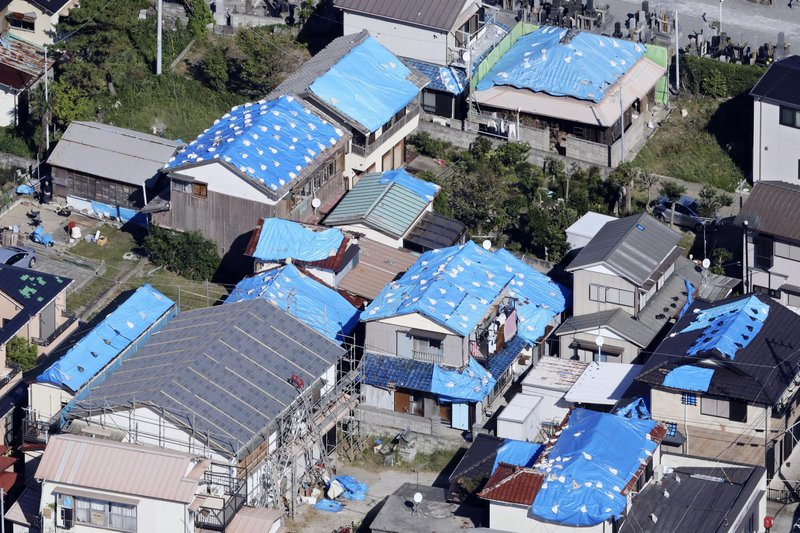 This Oct. 9, 2019, photo shows the sheet-covered roofs of the houses damaged by typhoon Faxai in Kyonan, near Tokyo.  Japan's weather agency is warning a powerful typhoon may bring torrential rains to central Japan over the weekend. (Kyodo News via AP)