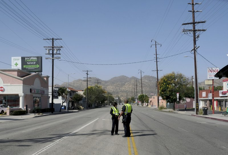 Strong Santa Ana winds in Chatsworth, CA., blew across power lines causing them to arc and transformers to explode. Power was out for street signs, businesses and residents. Two LAPD officers stand on a closed Devonshire St. at Owensmouth Ave., east of Topanga Canyon Blvd. on Thursday, Oct. 10, 2019. (Dean Musgrove/The Orange County Register via AP)
